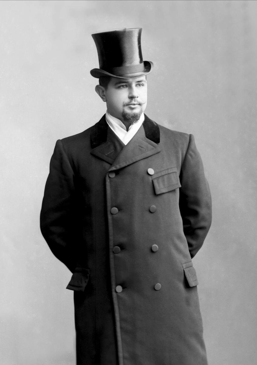 Portrett, mann i frakk og flosshatt. Kontorsjef Aass Andersen.