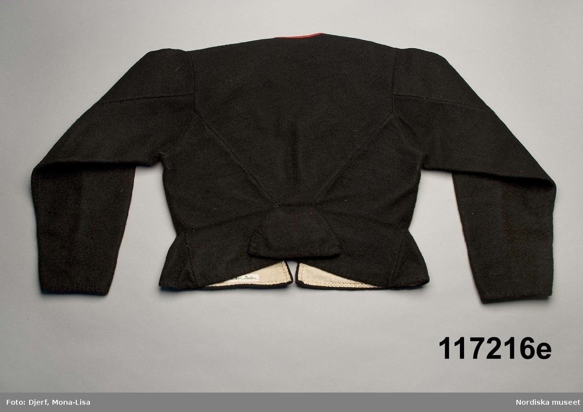 """Huvudliggaren: """"Sorgdräkt för kvinna. Särk med 'hängseltåg', 'särkyvdel'; vit -'häsklä'; blått livstycke; svart tröja; huvudduk; 'svart näsduk'; hatt; 'raskförklä', 'sockar',  'hårbandsvifsa', huvudbindel.""""  Bilaga: a: """"8 Särk, övdel. av linne eller blågarn. med broderade linningar på överdelen"""" c: """"11. Hvit häsklä."""" Anm: Kung Kerstin Larsdotters resa i Floda sn Dalarna 24/2 - 8/3 1912. Innehåller förteckning på inköp av dräktdelar från Floda, inv nr 117 216 - 117 239. Här finns  tillverkningstid och beskrivningar på vissa av dräktdelarna.  I vissa fall nämns också utförligt på vilka helgdagar dräktdelen  användes.  Katalogkort: a: Hängselsärk b. Överdel av halvlinne vävt i kypert. c.  Halskäde av småmönstrat bomullstyg, liknande kambris, vävt  i kypertvariation med drällmönster. d. Livstycke av mörkblå kraftig vadmal, e. Tröja av grov svart vadmal  i.   Mönstervävt band med upplockat mönster i rött z-tvinnat ullgarn på vit linnebotten, med hjärtan, kryss och rombformer, 2 band om vardera 124 cm har vikts och sytts ihop så att det ena bildar en ögla och det andra har fria ändar avslutade med en tofs i bandets garn. Läs mer om dräktskicket i Floda i: Albert Alm, Dräktalmanacka för Floda socken, Nordiska museet, Sthlm 1930 /Berit Eldvik 2005-04-14"""
