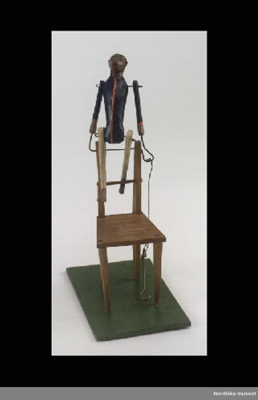 Inventering Sesam 1996-1999: H  13    L 12    B 7,5 (cm) Apa, halvmekanisk leksak, av trä, ståendes vid brunmålad stol av trä, på rektangulär bottenplatta (grönmålat trä); huvud med målade anletsdrag. Iklädd målad dräkt - blå överdel med långa ärmar, orange detaljer samt gulmålad benklädsel. Apans båda händer fästa vid ståltrådsanordning som fästs vid platsen för överstycket på stolen samt vid bottenplattan. Härifrån utgår en spak som, då man trycker den nedåt, gör att apan svänger upp på stolen, och ställer sig och bockar. Jmf. inv.nr. 279.435. Charlotta Dobson Hoffman jan 1998