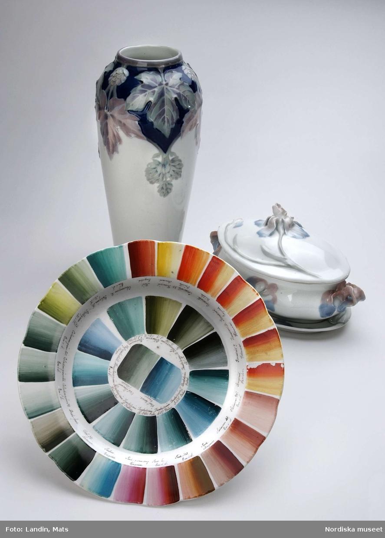 Porslinstallrik i en serie med uppmålade prover på underglasyrfärger med textförklaringar. Rörstrand, sign. B.Ä., daterad juni 1889. I bakgrunden vas och terrin med blomsterdekor.