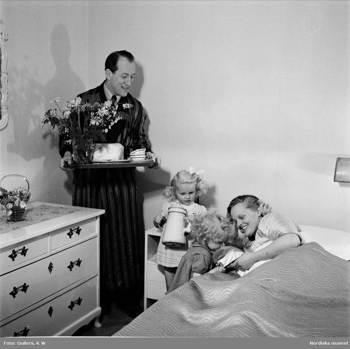 Mors dag. Två flickor och en man med kaffebricka uppvaktar mor vid sängen.