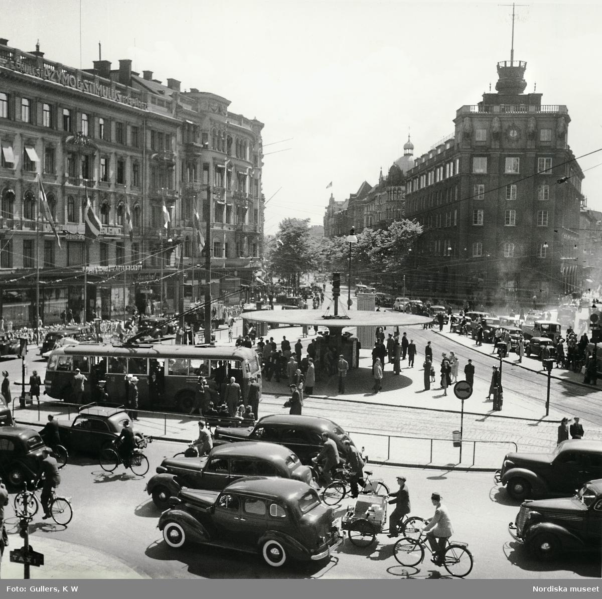 Stadsbild från Stureplan i Stockholm. Trafik och människor rör sig kring Svampen en solig sommardag.