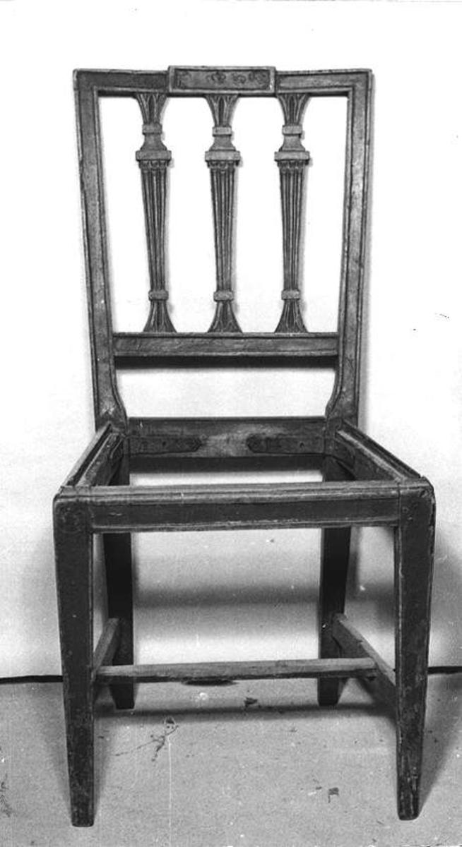 Två stolar av trä. Brunmålade. Under ett ljusare brunt färglager. Sargarna stadgade med järnband. Triangulära träförstärkningar har placerats mellan sidosargen och bakbenen.