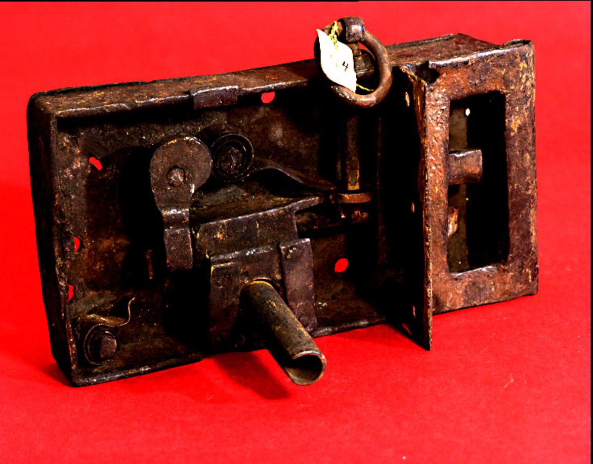 Lås av järn, s k fällbomslås. Ornamenterat låshus. Dubbla reglar varav en är avfasad. Den spärrande regeln kan lyftas med en ögla på låshusets ovansida.