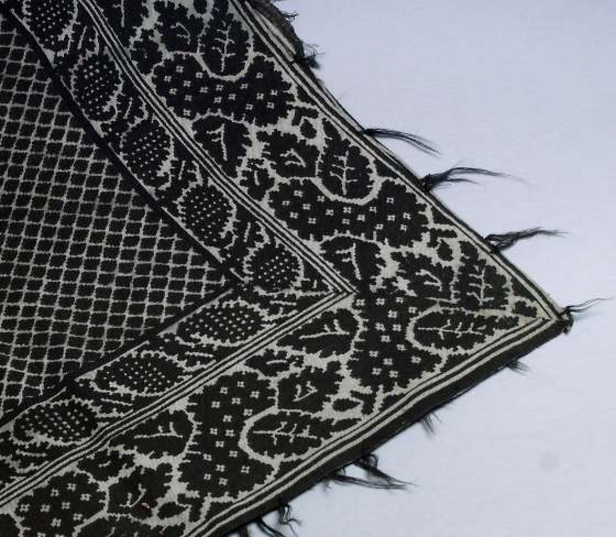 Kläde av kyprat bomullstyg. Vit bottenfärg med tryckt svart mönster. Iknutna fransar av svart ullgarn.