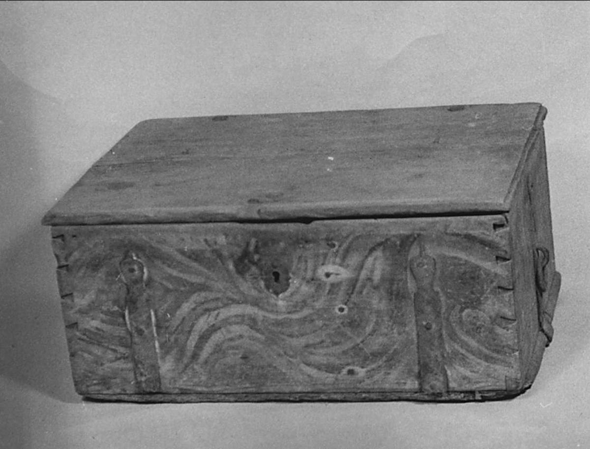 Kista av trä med marmorering i brunt, gul och svart. Beslag och bärringar av järn.