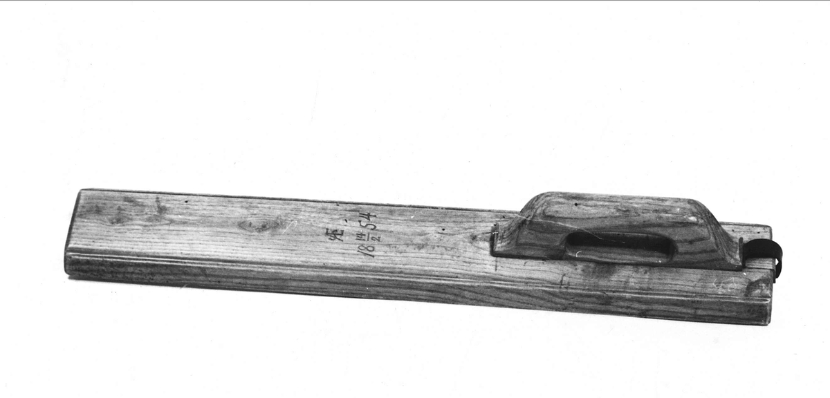 Mangelbräde av trä. Inristat: AE 18 14/2 54. Handtaget inlaxat. Läderrem för upphängning.