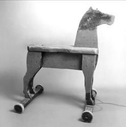 Häst av trä, tillverkad av brädor, står på två tvärställda brädor med hjul av trä i båda ändar.