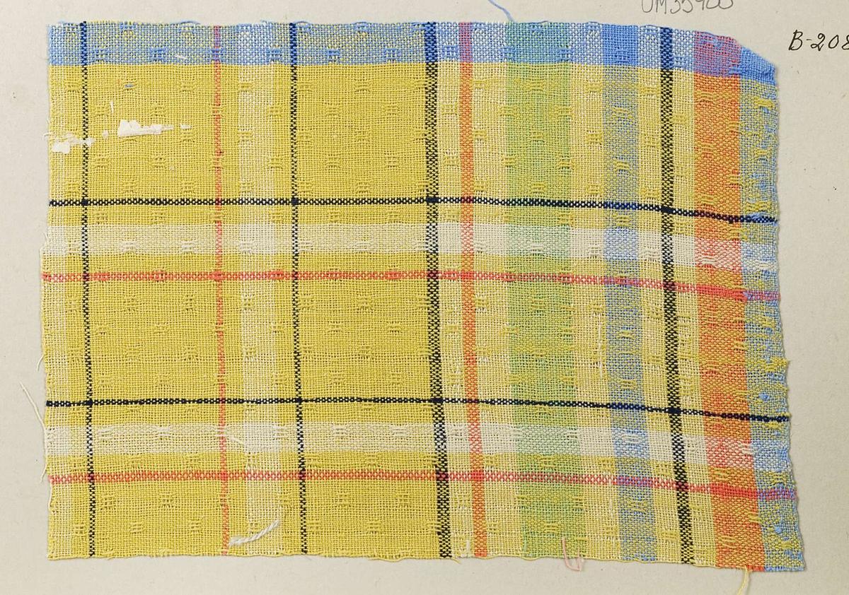 """Vävprov ämnat för dukväv vävt med bomullsgarn i gult, blått, svart, grönt och rött. Vävprovet har nummer """"B-2085""""."""