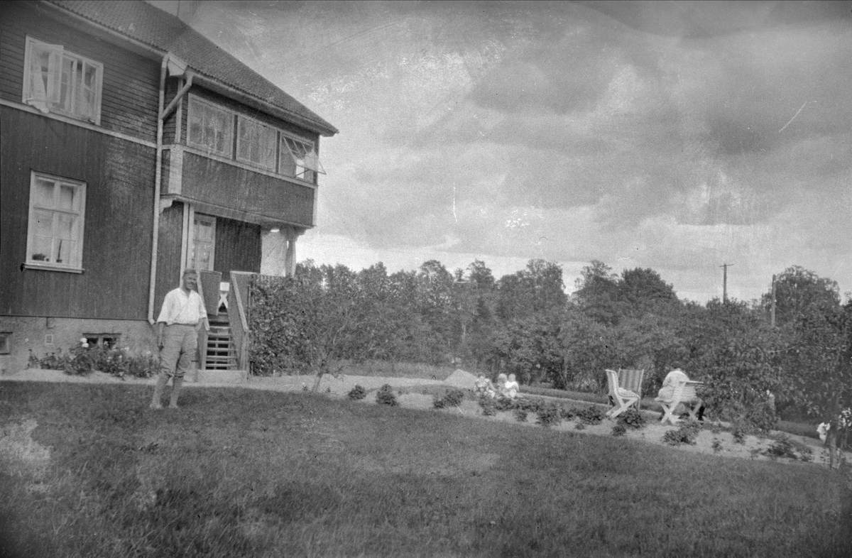 Man framför bostadshus, sannolikt Uppland 1940 - 50-tal