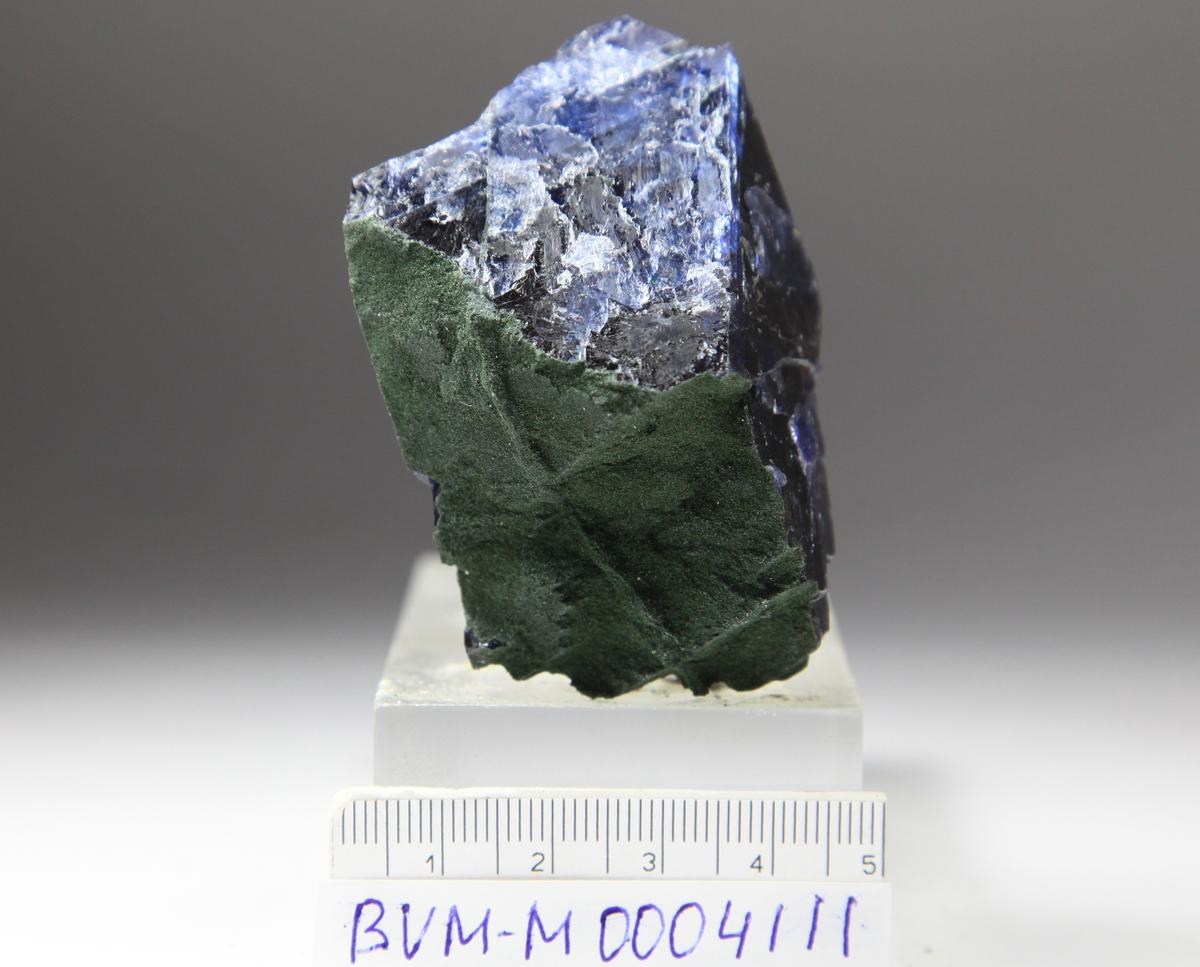 Fluoritt, blå, med finkornet kloritt, bruddstykke med oktaedrisk spaltbarhet - 2 oktaedriske bruddflater under kloritt.