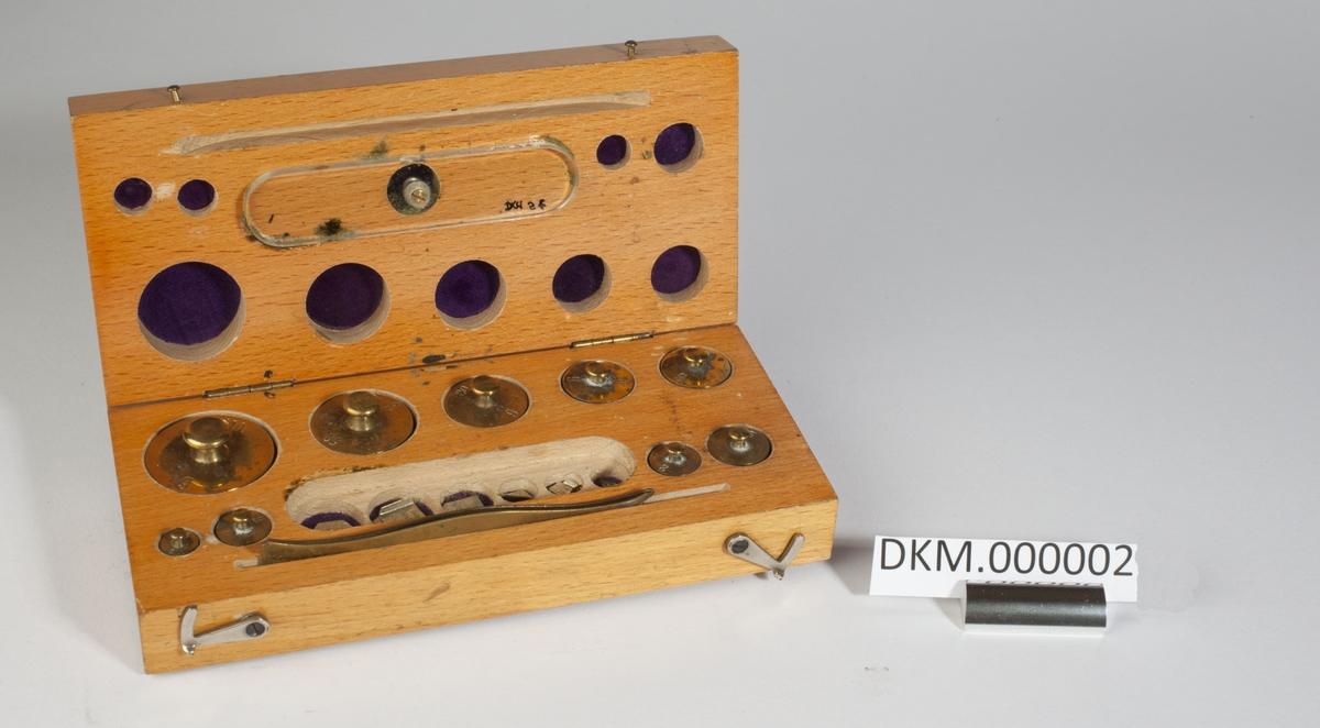 Kasse med lodd. Loddene er flate sylindere og plater. Vekten er stemplet inn i hvert lodd. Stempel fra kontrollen på plateloddene.