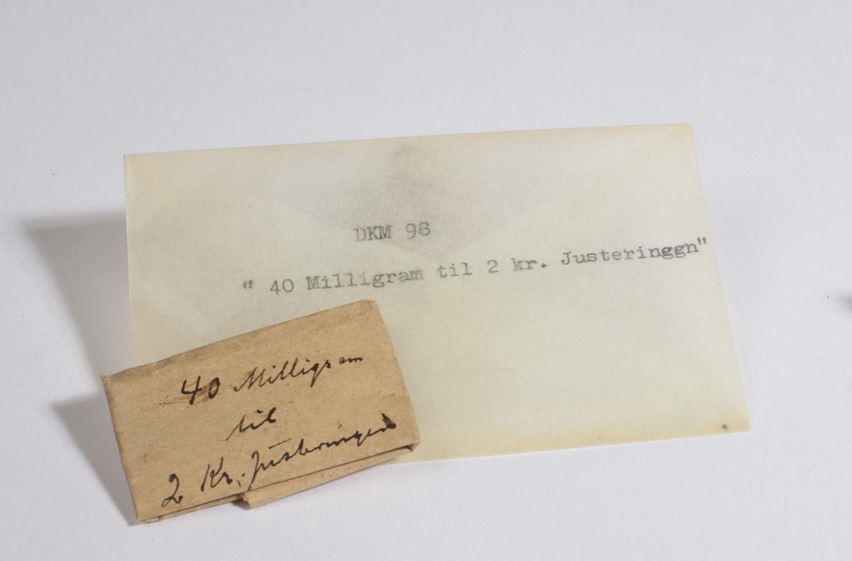 Papir brettet til en konvolutt som inneholder flere små metallbiter.