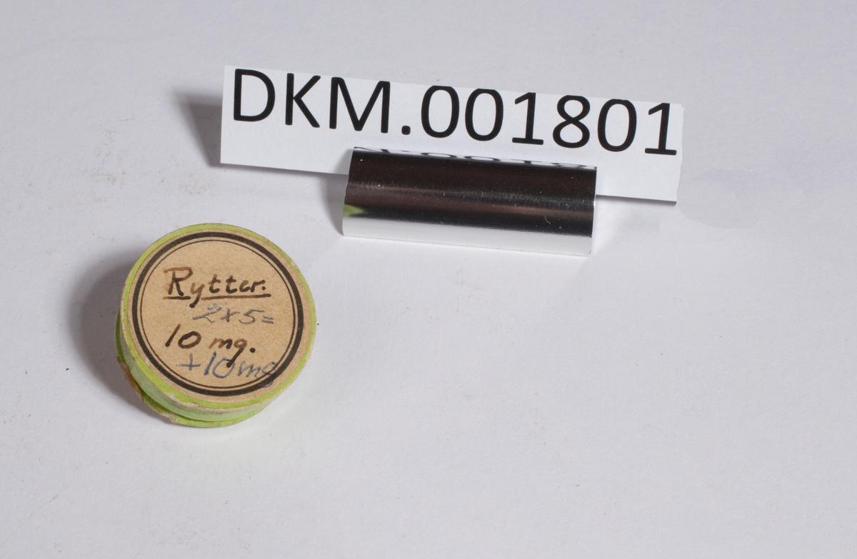Ett etui med en ti- milligrams metalltråd som er bøyd på midten og tvinnet ett par ganger rundt seg selv, samt to metalltråder som hver veier 5 mg.