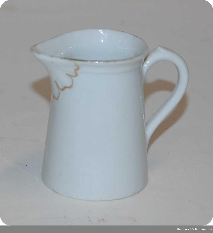 Fløtemugge av hvitt porselen. Gulldekor rundt tuten, langs kanten oppe og på hanken.