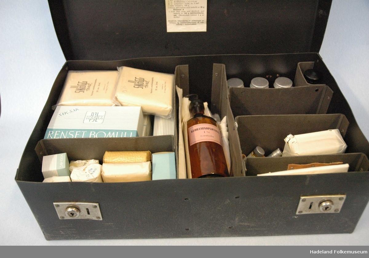 a) koffert i stiv papp. 2 stk lås i blankt metall med nøkkelhull.Kofferten inneholder 8 rom adskilt av pappvegger.  b) pinsett c) plaster