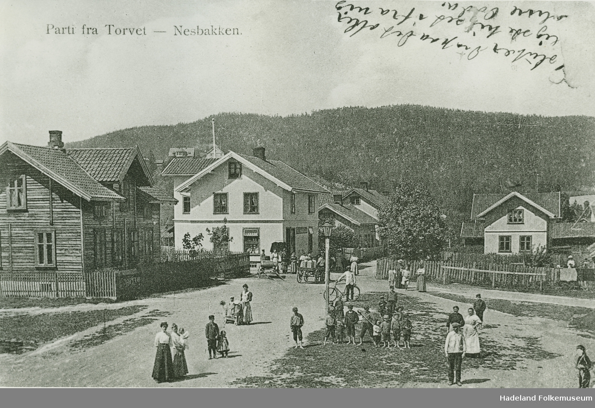 Parti fra torvet på Nesbakken med bygninger og personer oppstilt på torvet.