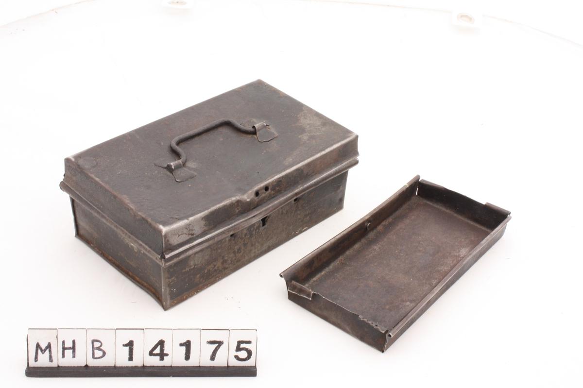 Rektangulært metallskrin der lokket er festet til skrinet langs øverste del av baksiden. På lokkets overside er et metallhåndtak. Under lokket, midt på skrinets fremside, er en nøkkelåpning. Det er også ett hull på hver side av nøkkelåpningen, og to hull like over i lokket.   Inni skrinet er en rektangulær del med stående sider og to små hekter i hver kortside.