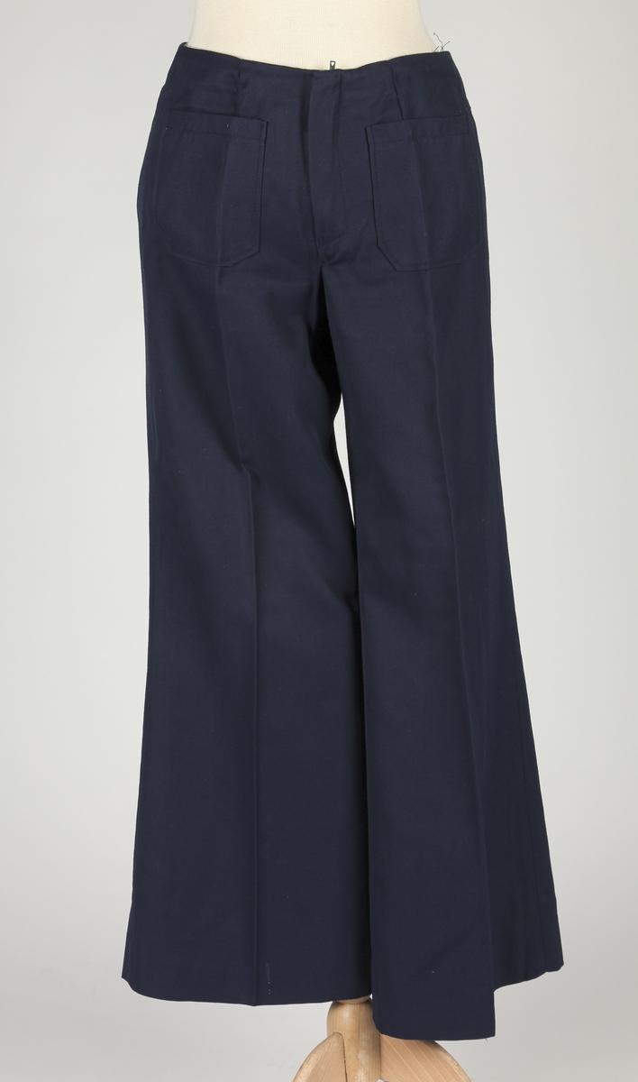 Bukse med sleng i bena. Beltebånd i livet, påsydd lomme foran.