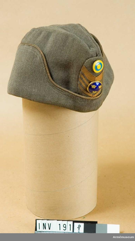"""Mössan är tillverkad av gråbrungrönt ylletyg med ett yttre uppslag och en inre svettrem. Mössmärke m/1952 för överste  utgörs av på ett ellipsformat underlag utan styvnad anbringade  galoner i metallfärg och däröver en i emalj, trekronorsknapp. I  övre delen av ellipsformen finns en nationalitetsknapp i emalj. Insidan fodrad med bomullsatin och märkt """"Kungl. Hovleverantör  Mea Egen tillverkning Stockholm"""". En svart 6 mm bred resår är  fäst från insidan."""