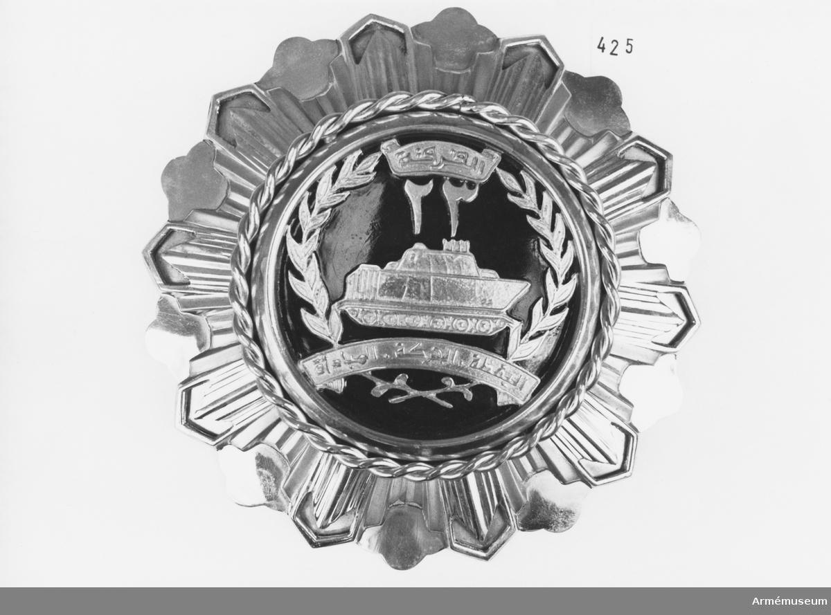 """Samhörande nr är 294-299, 321-350, 400-448 (425-426). Sköld från 2. egyptiska armén (Kanthara). I mörkrött sammetsfodral. Mottagen vid besök i smb med inspektion av svenska UNEF-kontingenten nov 1974. Av mässing, formad som en utslagen blomma. Bottenplåten är hamrad, över den en stansad plåt i strålform. Över detta en """"snodd"""" som inramar emblemet. Emblemets botten är svartmålad med guldplåtsinsignier; stridsvagn, krans och banderoller med egyptisk text. Stöd på baksidan."""