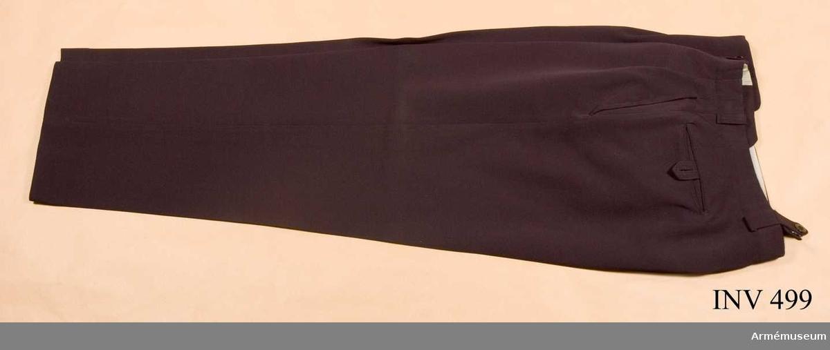 Storlek C 96. Av yllediagonal med snedskurna och insydda fickor fram och bak rakskurna och infällda. Tio st svarta knappar finns varav fem sitter i julpen. Hängselstroppar finns.