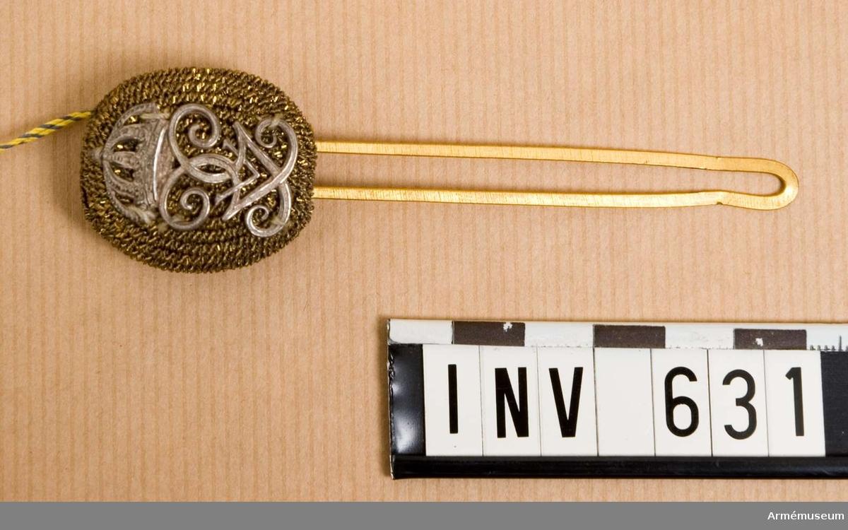 Av guld med H.M.Konungens namnchiffer i silver. Fästes i huvudbonaden med pomponghållare. Pompongen är kupad och har framsidan täckt med guldsnodd. Därpå Gustaf V:s namnchiffer i silver, 30 mm högt. Stommen är gjord i plåt överdragen med ett ganska tätt nät av guldtråd som är synligt på baksidan. Hål för hållaren. Ett gult sidenfoder är synligt under nätet. Hållaren är gjord av gulmetall och upptill försedd med en liten oval platta som skall tjäna som stöd för pompongen. Två skänklar utgår från den ovala plattan och skall användas till att sticka genom pompongen, bakom vapenplåten och genom mössan. Hålles fast med knappen. Användes av infanteriet vid parad.