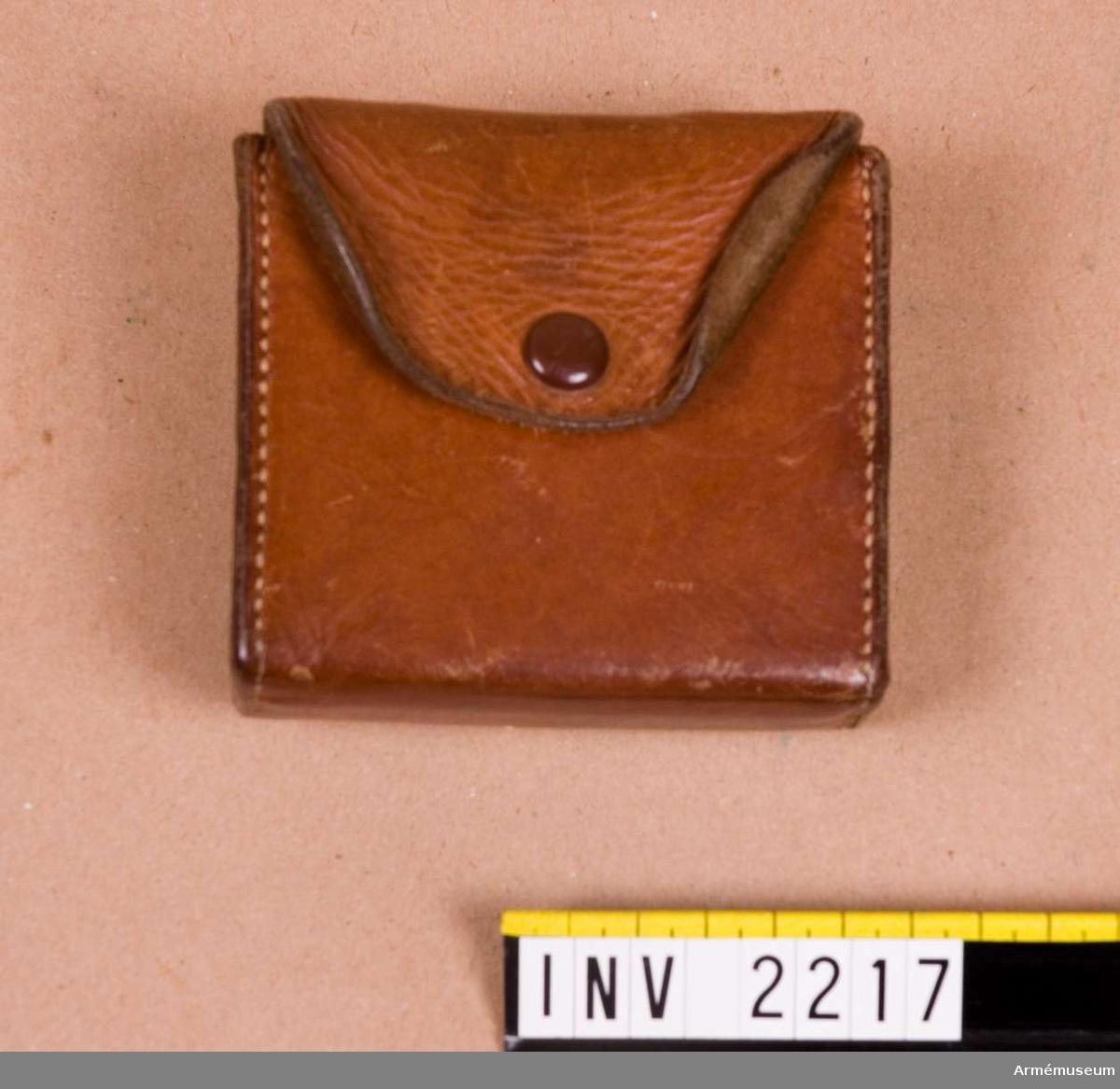 Samhörande nr är 2266-2169, 2214-2220 (2216-2217).Fodral t kompass. 1950.Ljust läder med laskade sömmar. Lock med flik, knäppt med  tryckknapp. På baksidan en hälla för att dra genom en livrem.Har tillhört ryttmästare J Henke, numera boende i Marbella, Malaga, svensk konsul.