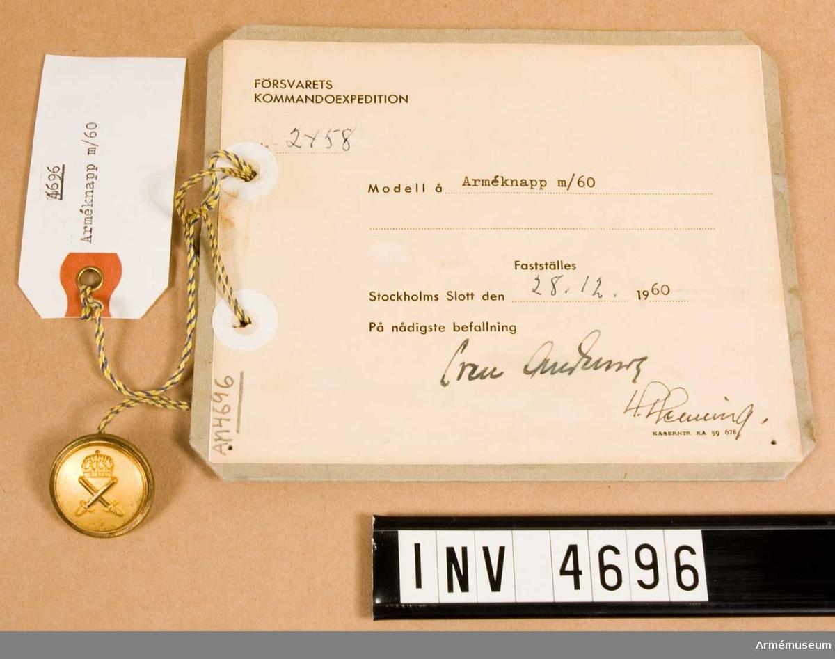 Arméknapp m/1960 tillverkad av metall och utförd i guldfärg. Kanten är omvikt polerad. Armétecknet är placerat på slät, ej polerad yta (bild 31).Tecknet anlades av fast anställd personal, stor till vapenrock  m/1960 och m/1961, liten till axelklaffar och skärmmössor, vid förband organiserade för FN:s räkning. Det anskaffades åren 1960 - 1976. För att nedbringa såväl kostnader som sortiment bestämdes sistnämnda år att knapp m/1939-1960 guldfärg (kronknapp) skulle ersätta arméknappen, men fick denna användas så länge tillgång fanns. Vidhängande etikett anger dag för fastställande: 'Stockholms Slott 28/12 1960 Sven Andersson  H. Henning'. < 19601228 >.
