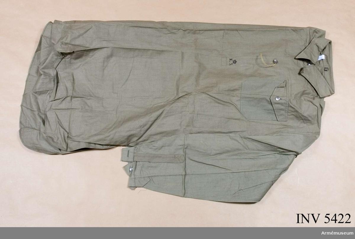 """Stl 44. Gråbrungrön m fast krage och linning vid ärmen. Knäppes i sprund m två kompositionsknappar. Märkt på sprundet  """"K 3"""" krönt m kunglig krona. På innersidan av kragståndet märkt  """"Taba 44, K 3"""" krönt m kunglig krona. Användes t uniform  m/1939, daglig dräkt."""