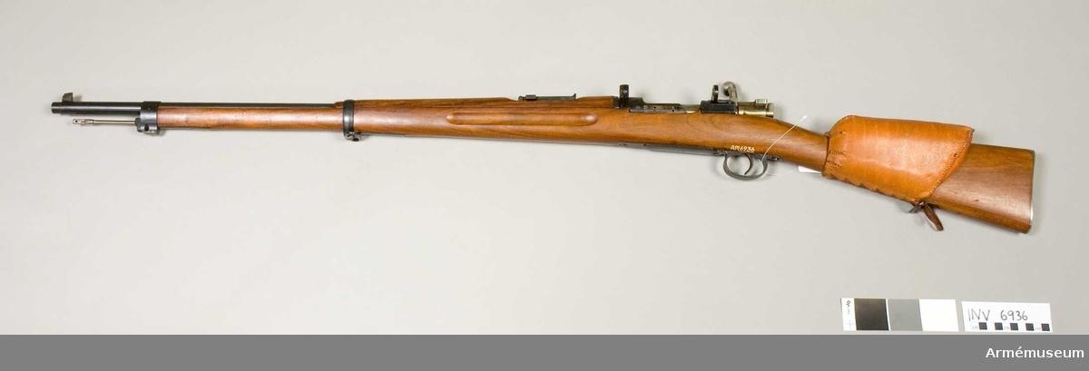 Gevär m/1896, system Mauser, med hållare för kikarsikte försöksmodell och kindstöd av läder. Tillverkningsnr 25852. Märkbricka saknas från kolven. Slutstyckets handtag är böjt nedåt. Märkt J.V. 25 852. Hållare för kikarsikte tillverkad av Husqvarna vapenfabrik, Huskvarna. Bakplåtens nr 4716. Kikarsikte med fodral 1975:8381 - 8382 passar detta vapen. Består av 1 st gevär m/1896, 1 st kindstöd av läder.
