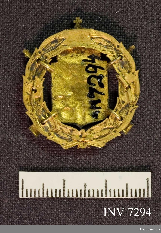 Ett förgyllt märke med riksvapnet i blått och guld, krönt med kunglig krona. Erövrat av givaren efter 35 gångers skjutning.