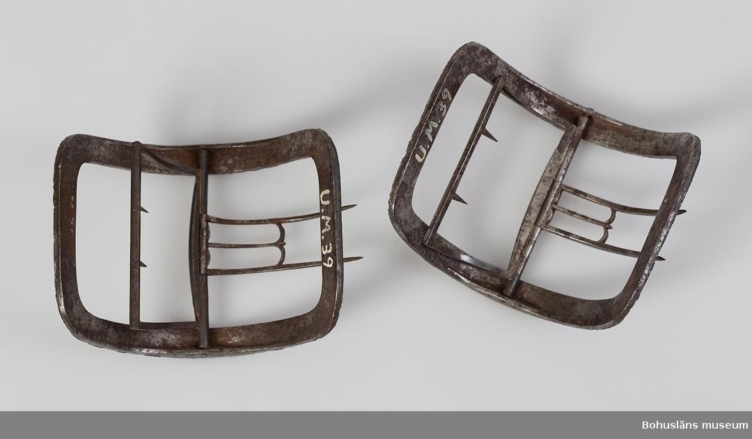 Ett par kraftigt bågformiga skospännen, troligen från den gustavianska eran. Spännen av järn vars översida har fått ett gjutet dekorerat skikt utav en legering av vitmetall. Mönster i form av blad- och blomornament. Lätt rost på järndelarna.  I övrigt hela. G:30 i 1869 års tryckta katalog.  Ur handskrivna katalogen 1957-1958: Skospännen av stål Mått c:a 8 x 7 cm. Stål, utsirade med lövbård. Rostiga, för övrigt oskadda.  Lappkatalog:78