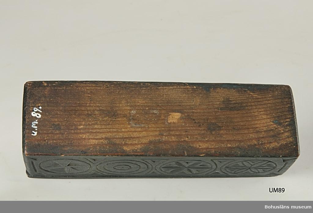 """Rektangulär låda med skjutlock. Locket och nederdelens långsidor är täckt med geometrisk dekor bestående av rosetter, runda ringar och inskrivna kors. Sekundärt svartmålad, har bets undertill. På lockets undersida är initialerna """"EBS"""" inskurna. En äldre """"frimärks""""etikett med """"Lycke Håby"""" sitter limmad intill.  Litt.; Gjaerder, Per, Esker og tiner, C. Huitfeldts förlag, Oslo, 1981, s. 48-50.  Se Knut Adrian Andersons """"Katalog I, A. yngre föremål"""" under Uddevalla museum/förening D 2A:1 i arkivet.  Ur handskrivna katalogen 1957-1958: """"Trälåda med skjutlock. Bottenmått 20,5 x 6 H. 5,5 Trä Svartmålad. Föremålet helt. Lycke, Håby, Bohusl.""""  Lappkatalog: 84"""