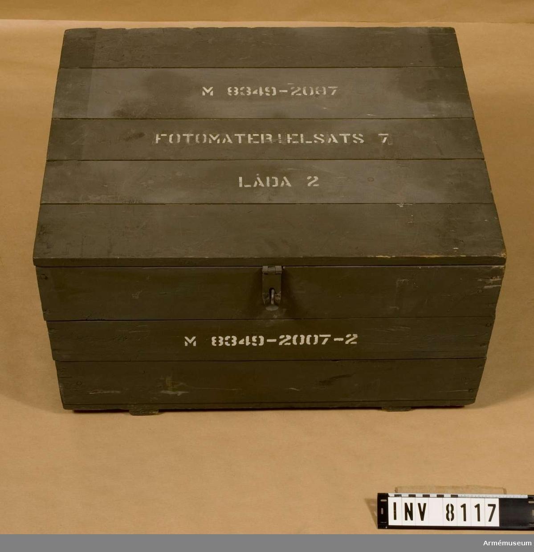 Låda av trä, målad grön utanpå. Gult trä inne i lådan.  Lock med gångjärn.  Innehåller satskort.  M 8349-2007-2.Innehåller utrustning för fotomaterielsats 7 låda 2, 25 föremål,  AM-nr 1975:8117-8141.