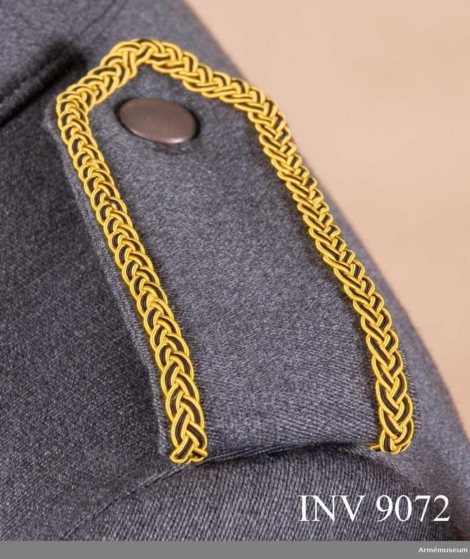 Av samma tyg och färg som jackan kantad med en flätad galon i gult och svart silke. Tecken för kårchef. Axelklaffen är dubbel och viks runt en träns vid axelsömnen och knäpps mot en grå knapp av mindre modellen på jackan.