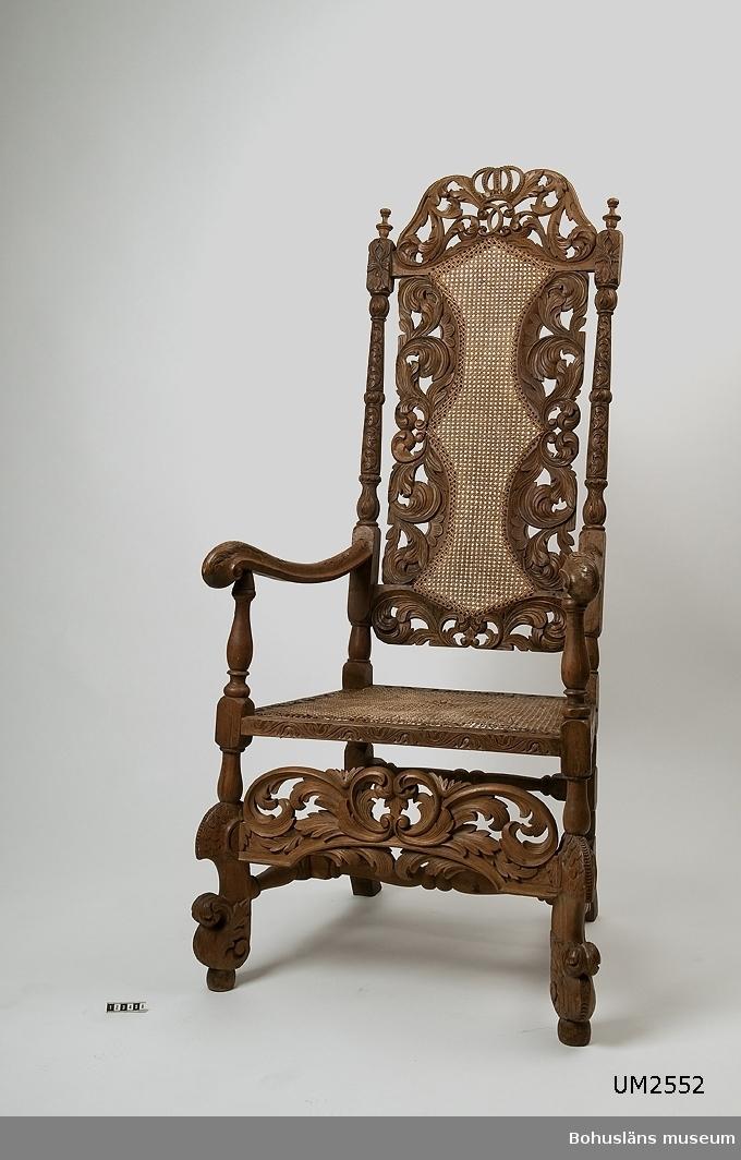 Armlänstol av engelsk-holländsk typ, troligen i valnöt med flätad rottingsits. Ryggstödet prytt med Karl XI:s krönta namnchiffer. Tillverkade under den karolinska tiden. Svarvade ben, benkryss och ryggstolpar. Snidade framben, genombruten framslå och en rikt snidad ryggbricka. Sits och rygg är rottingflätade. Delar av stolens trä är kompletterat. Träslag är troligen valnöt och i de kompletterade delarna björk.  Ur Knut Adrian Anderssons katalog III 1917: No 4. Den ena av två stolar i barockstil med kunglig krona på det höga ryggstödets överdel; rikt utskuren. Den är troligen en bland dem, vilka lära  tillhört fältmarskalken Greve Rutger von Aschebergs gods Gullmarsberg i slutet av 1670-talet. Skänktes 1862?/1872? till Uddevalla museum av herr L. Wesslau å Gullmarsberg.  Ur handskrivna katalogen 1957-1958: Länstol i barock Carl XIs namnchiffer. H. 138; sitsens mått: 45,5 x 58 cm; engelsk typ m. rottingflätn. i sits och ryggstöd. Sitsen trasig, en del saknas överst på ryggstödets krona. Maskhål.