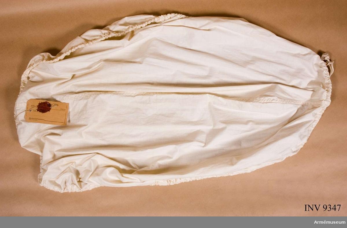 Samhörande nr är 9345-9347. Överdrag m/1940 till ryggsäck, ur snödräkt.Sydd med en söm mitt på och med en dragsko runt kanten  genomdragen med en vit snodd.