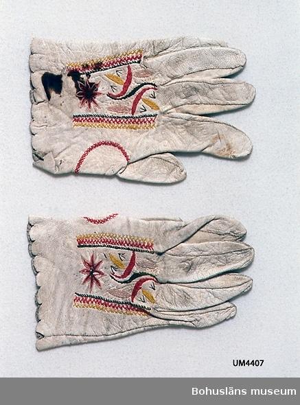 Handgjorda handskar av vitt skinn med broderi i bomullsgarn och silke i rött, ljust rosa, grönt, ljust gråbrunt och gultonat vitt. Broderi i plattsöm, flätsöm och raka stygn finns på ovansidan. Sömmen runt tummen är markerad med en flätsöm. Tillverkningstid och användningstid uppskattade.  Vantarna är märkta UM4407 a och b. Den blivande bruden fick så kallade brudhandskar som gåva av fästmannen. Hon skulle bära dem på bröllopet, men de användes även senare till högtid. Slitna. Två stora bruna fläckar på ovansidan av ena handsken. En del av broderiets tråd bortsliten. Smutsiga.  Litteratur: Nylén, Anna-Maja, Folkdräkter ur Nordiska  museets samlingar, Nordiska museets handlingar 77, Lund 1971, sid. 67-70.  Takhimlar och brudhandskar Folklig textiltradition i Västergötland, Widhja, Inger, Skrifter från Skaraborgs länsmuseum nr 12, Skara 1990, sid. 132-133.  Ur handskrivna katalogen 1957-1958: Ett par brudhandskar L. c:a 18 cm; vitt skinn m. broderi i ylle; ngt smutsiga, på b) två mörka? fläckar. Hela.