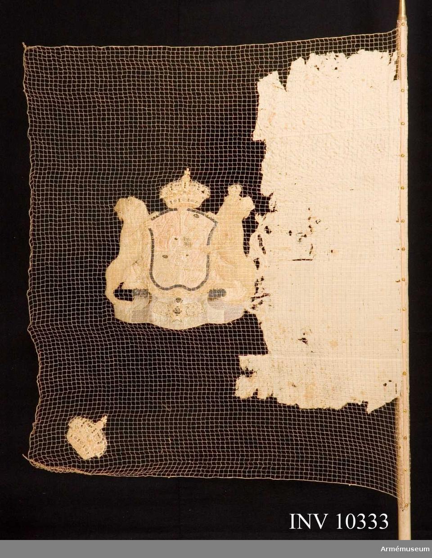 Grupp B I.  Duken av sidenkypert i tre våder, vit, broderat lika på båda sidor svenska riksvapnet under Holstein-Gottorpska husets vapen samt slutna kronor i hörnen. Skölden guldkantad, behängd med serafimerkedjan och krönt med en sluten kunglig krona i silke med något guld. Sköldhållarna, lejon, dubbelsvansade och bakåtseende, krönta med slutna kronor, jämte skölden vilande på ett postament. Stång av furu, vitmålad, längd 2,95 m, diameter upptill 2,8 cm, nedtill 3,5 cm. Holk av förgylld  mässing. Spets av förgylld mässing med Carl XIV Johans krönta namnchiffer, infattat av två mot varandra i lyrform böjda palmkvistar, upptill förenade i en strålande sol. Längd 15,5cm.  Spetsens monogram med två C:n är troligen ändrad från Carl  XIII.