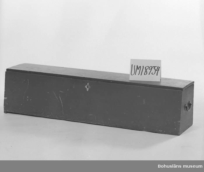 Grönmålad kista med metallbeslag och handtag. Raka kanter, ingen dekor. ::