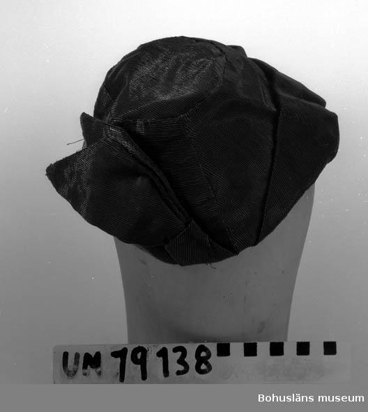 471 Tillverkningstid 1950-TAL 394 Landskap BOHUSLÄN  Hatt utan brätte i svart glansigt material. Uppvikt kant. Rosett.  Se UM19130.