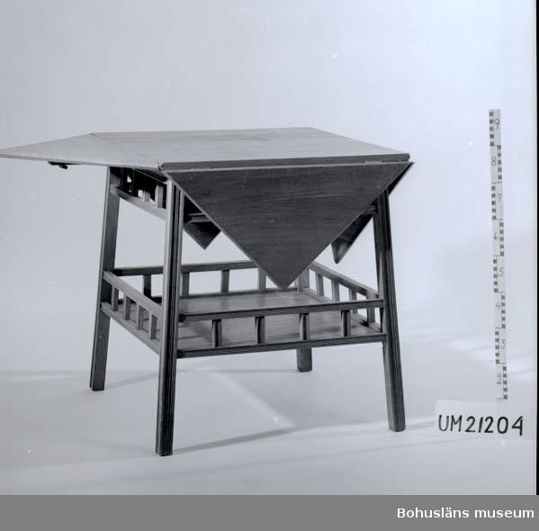 Fyrsidigt bord med fyra klaffar. Listhyvlade ben. Försett med hylla undertill.