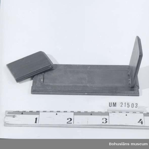 594 Landskap BOHUSLÄN  Bokstället består av en brunbetsad platta hopsatt med två längsgående snidade ramar och två gavlar. Två klaffar, en i vardera ändar, fastsatta med två gångjärn. Klaffarna är fällbara.  UMFF 26:2
