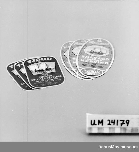 594 Landskap BOHUSLÄN  Två olika motiv och texter för sill. Engelsk text. En etikett är oval, den andra är fyrkantig med rundade hörn.