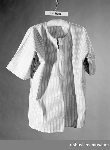 Lång-randig i ljusblått, vitt och grått. Sprund i halsen med en knapp. Kraglös. Brukaren är givarens man. Lennart Corneliusson född 1908.