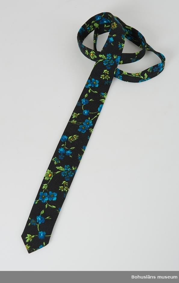 Svart botten. Klarblå blommor och gröna blad.