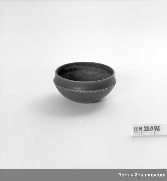 Brun stengodsliknande glasyr. Utåtbuktande rund form.  Regelbundna intryck (små, ovala) längst kant på utsidan. Rak rand. Storsäljare enligt Åke Jaking (1923-2007) .