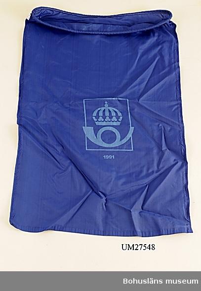 """Postsäck av mörkblå nylon, runt öppningen förstärkt med invändigt tunt rep. På framsidan märkt i ljusblått med Postens logo, ett krönt posthorn och med årtalet 1991.  Postsäcken ingår i insamlingen i projektet Moderna skärgårdsbor, UM27511 - UM27595 och kommer från Dyngö  För övrigt material från Fjällbackaarkipelagen/Kiddön och Dyngö, se UM27521 - UM27523, UM27539 - UM27550; UM27521 Hummertina med flöte och väle (Bilaga artikel Bohusläningen 2006) UM27522 Hummertina med flöte och väle UM27523 Hummertina med flöte och väle UM27539 Plysch-anka Bohustrafiken """"Väderö skräck"""" UM27540 Solglasögon UM27541 Tidtabell UM27542 Broschyr """"Vad kostar resan"""" UM27543 Färdbiljett, 2 st UM27544 Visitkort UM27545 Flagga Västtrafik, trasig UM27546 Ismejsel UM27547 Isätare  UM27548 Postsäck UM27549 Postsäck UM27550 Postsäck  För information om projektet Moderna Skärgårdsbor, se UM027511.  Litteratur: Sjöholm, Carina. Moderna skärgårdsbor i gammal kultur.  Skrifter utgivna av Bohusläns museum och Bohusläns hembygdsförbund nr 73. Bohusläns museums förlag.  Avsnittet om Fjällbackaarkipelagen s. 101- 120."""