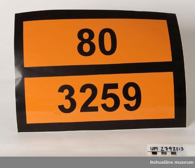 """Föremål  insamlade i projektet Oil Field Girls - petrokemisk industri i Stenungsund 2003-2004.  Exempel på etiketter av förklistrat plastat papper att fästa på plåtfat. Avser märkning av plåtfat innehållande ETHOMEET C/14 Kokosalkylaminetoxilat Två vita avlånga likadana etiketter med svart text, tillverkad för Akzo Nobel Surface Chemistry AB.  I övrigt märkta med omfattande text, bl. a orange varningstext  märkt """"Hälsoskadligt"""" och """"Miljöfarlig"""" på flera språk och """"Mycket gifitg för vattenlevande organismer, kan orsaka skadliga långtidseffekter i vattenmiljön."""" Weight: 195 kg Oanväna.  Etikettsystemet som gällt fram till år 2002 har inneburit ca. 5 etiketter  per fat. Det nya systemet innebär att all information finns på en jättelång etikett som skall sitta på sidan av faten eftersom man i framtiden  skall lagra faten stående.  Sammanhör med UM27920.  Föremålen är resultatet av en direkt inbjudan till deltagarna i projektet att föreslå föremål som skulle kunna samlas in till museet. Plåtfaten finns med i webbutställningen men det var insamlingsgruppen som föreslog att vi skulle ta in ett plåtfat till museet. En väldigt liten del av Akzo Nobels produkter levereras  annars i fat, det mesta går via rör till båtar i hamnen. Det är väldigt speciella produkter som sänds i fat.   Föremålen UM27901 ff. ingår i Delprojekt I : Oil Field Girls - petrokemisk industri i Stenungsund, ett metodutvecklingsprojekt kring den petrokemiska industrin i Stenungsund. Bohusläns museum har i projektet velat pröva och utveckla en metod, där olika grupper i Stenungsund och på industrierna involverats i en insamlingsverksamhet kring Stenungsunds industriella näringsliv och petrokemiska tillverkning."""